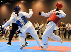 """0982-RiderKOsKing9148.jpg: U.S. Army World Class Athlete Program martial artist Sgt. William Rider delivers a knockout kick to the ribs of Californian Cory King with 1 minute, 3 seconds remaining in the second round of their featherweight semifinal match at the 2009 U.S. National Taekwondo Championships July 5 at the Austin Convention Center in Texas. """"In my 25 years of Taekwondo, I think that's the second time I've ever seen a body shot knockout, and the first from a roundhouse kick,"""" WCAP Taekwondo coach David Bartlett said. """"I have to give thanks to the strength and conditioning program of Master Sgt. Mike Mielke."""" Photo by Tim Hipps, FMWRC Public Affairs"""